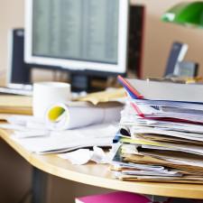Biurko ze stosem dokumentów i książek
