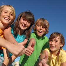 Uśmiechnięta grupa dzieci z kciukami podniesionymi w gorę.