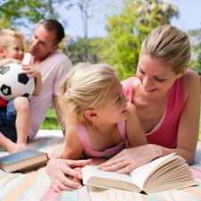 Matka z dzieckiem, czytają książkę wraz z rodziną w tle.